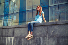 Positive Caucasian girl in sunglasses sitting on concrete bench Royalty Free Stock Photography