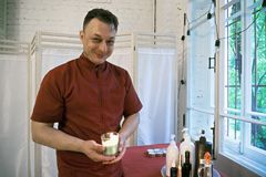 Positive masseur with candle Stock Image