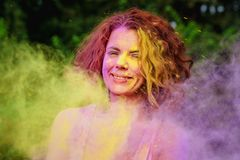 Positive caucasian model with curly hair posing in a cloud of pu. Positive caucasian woman with curly hair posing in a cloud of purple and yellow Holi paint royalty free stock photography