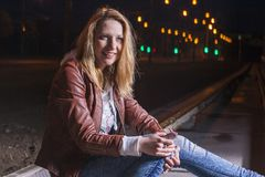 Positive Caucasian Woman In Leather Jacket and Blue Jeans. Playing on Rails With Bag Outdoors at Night.Listening To Music player. Halogen and Flash Lights are Royalty Free Stock Photos