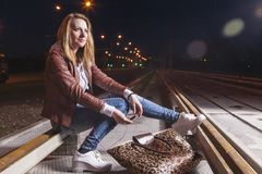 Positive Caucasian Woman In Leather Jacket and Blue Jeans. Playing on Rails With Bag Outdoors at Night.Halogen and Flash Lights are Used. Horizontal Image Royalty Free Stock Photography