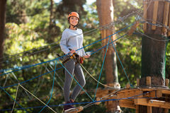 Positive charming woman standing on the rope ladder Royalty Free Stock Photo