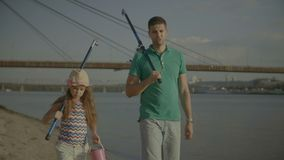 Dad and child with fishing rods walking on riverbank stock footage