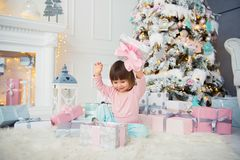Positive cheerful baby girl sitting with Christmas gift near Christmas tree. Happy New Year.  Stock Photography