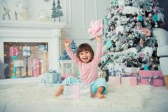 Positive cheerful baby girl sitting with Christmas gift near Christmas tree. Happy New Year.  Royalty Free Stock Photography