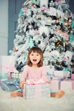 Positive cheerful baby girl sitting with Christmas gift near Christmas tree. Happy New Year.  Royalty Free Stock Photos