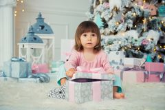 Positive cheerful baby girl sitting with Christmas gift near Christmas tree. Happy New Year.  Stock Image