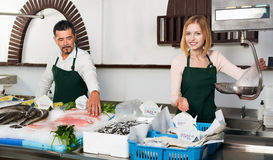 Positive cheerful cute shop assistants selling fresh fish Royalty Free Stock Photography