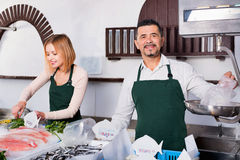 Positive cheerful cute shop assistants selling fresh fish. And chilled seafood stock photography