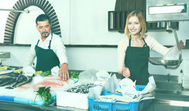 Positive cheerful cute shop assistants selling fresh fish. And chilled seafood royalty free stock image