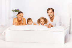 Positive cheerful family laying on white bed. In white pajamas together in the morning Stock Photography