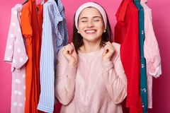 Positive cheerful gorgeous female with closed eyes in boutiqe. Lots hangers with outfits. Smiling lady finds what she needs. Woman. With toothy smile looks stock photos