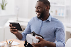 Positive cheerful man looking at the tablet screen Stock Photos