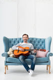 Positive cheerful man playing the guitar Royalty Free Stock Photos
