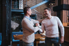 Positive cheerful men greeting each other Royalty Free Stock Image