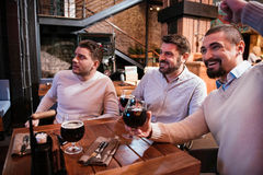 Positive cheerful men watching football. Sports games. Positive cheerful handsome men watching football and drinking beer while resting after work in the pub Stock Photo