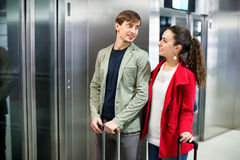 Positive cheerful  people with luggage standing at metro. Terminal elevator Royalty Free Stock Images