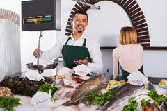 Positive cheerful shop assistants selling fresh fish. And chilled seafood royalty free stock photography