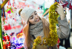 Positive cheerful woman at fair near counter with Christmas gift royalty free stock photos