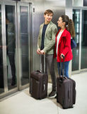 Positive cheerful young people with luggage standing at metro Stock Photography