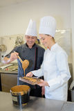 Positive chef with assistant cooking at kitchen in restaurant Royalty Free Stock Photography