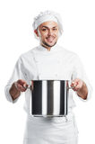 Positive chef with pan pot isolated. Smiling young adult chief with metal pan pot in his hand isolated Stock Photography