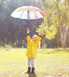 Positive child with colorful umbrella having fun Royalty Free Stock Image