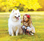 Positive child and dog having fun outdoors Royalty Free Stock Photo