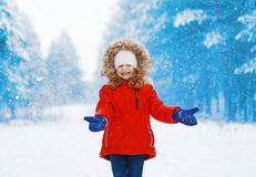 Positive child having fun outdoors with snowball in winter Royalty Free Stock Image