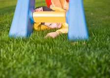 Positive child lay on grass near slide Royalty Free Stock Photo