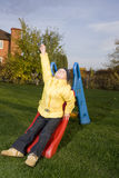 Positive child sit on slide with  green grass aro Royalty Free Stock Photo