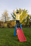 Positive child stay on slide with  green grass ar Royalty Free Stock Photography