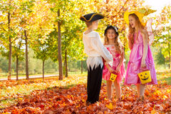 Positive children in Halloween costumes talking Stock Photos