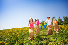 Positive children jump in sacks and playing. Positive children jump in sacks while playing together in meadow with dandelions stock photo