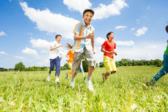 Positive children playing and running outside. Positive children playing and running in the field in summer Royalty Free Stock Images