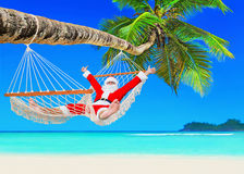 Positive Christmas Santa Claus relax in hammock at palm beach. Santa Claus relax at sun in white cozy mesh hammock thumbs up positive gesturing under coconut Royalty Free Stock Photos