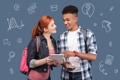 Positive classmates smiling and discussing their modern gadgets. Friendly classmates. Friendly positive classmates standing together and looking happy while Royalty Free Stock Image