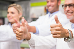 Positive co-workers standing with thumbs up Royalty Free Stock Image