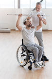 Positive coach teaching and helping the invalid in the gym. Disabled rehabilitation in process. Involved proficient aged general practitioner helping the Royalty Free Stock Image