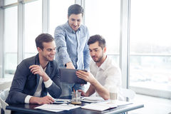 Positive colleagues discussing project Stock Image