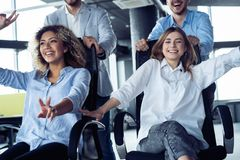 Positive colleagues having fun with office chairs. royalty free stock images