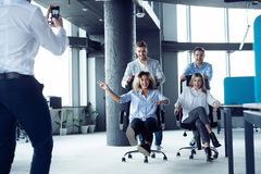 Positive colleagues having fun with office chairs. stock photos