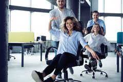 Positive colleagues having fun with office chairs. royalty free stock image