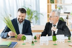 Positive colleagues looking at the bunch of herbs and smiling cheerfully. Funny activity. Friendly colleagues in a real estate agency sitting at the table and stock image