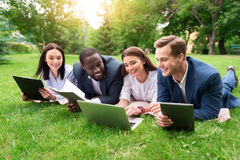 Positive colleagues sitting on the grass Stock Images