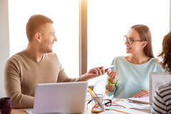 Positive colleagues sitting at the table. Pleasant interlocutor. Positive cheerful smiling colleagues sitting at the table and talking while working in the Royalty Free Stock Image