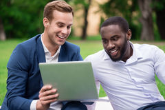 Positive colleagues using laptop. Modern users. Cheerful smiling pleasant colleagues using laptop and sitting on the grass while talking Royalty Free Stock Image