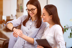 Positive colleagues  using smart watch. Royalty Free Stock Image