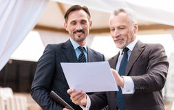 Positive colleagues working with papers. Involved in project. Cheerful content smiling colleagues talking and working with papers while expressing gladness royalty free stock image