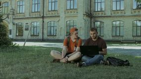College students working on laptop on campus lawn. Positive college male friends studying together with laptop and discussing university project while sitting on stock video footage